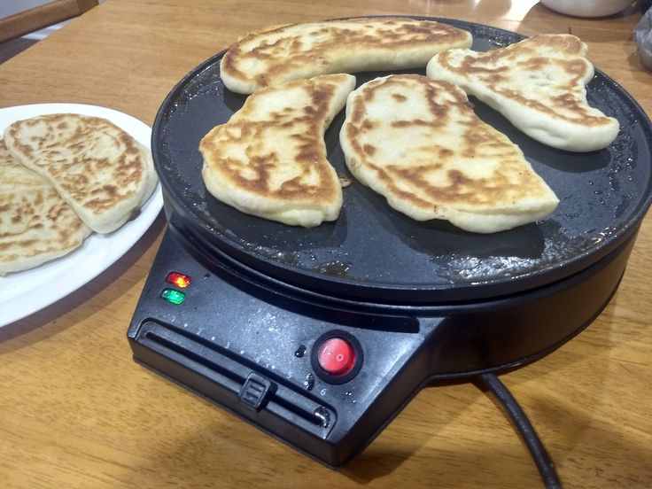 Frying roti naan with garlic and cumin on a crepe maker.