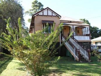 Weatherboard queenslander house exterior with bay windows & window awnings - House Facade photo 525993