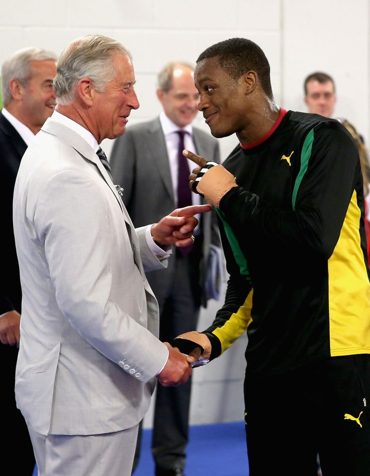 Prince Charles, Prince of Wales shares a joke with a member of the Jamaican Commonwealth Boxing Team as he visits the Emirates Arena and Chris Hoy Velodrome ahead of the start of the Commonwealth games on July 23, 2014