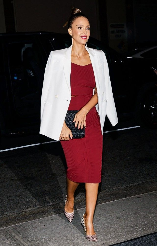 Jessica Alba wears a burgundy crop top, matching pencil skirt, white blazer, long earrings, printed leather heels, and a black woven clutch