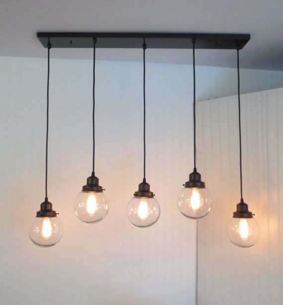 A perfect chandelier style for over an island or over a dining table. The five lights in a linear pattern will stretch the light from end to end, giving great illumination.Shown here with the vintage inspired 'squirrel cage' Edison filament light bulb. These bulbs are so awesome when placement on a dimmer.  * 5 1/2 Clear machine blown globes * Lengths of 36, 32 & 30 (still adjustable) * 36 Rectangular Canopy (Hardware Included) * 60 watt max.Edison bulb (not included) * Hardwired Ins...