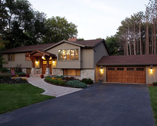 The stain on the pillars and garage doors adds depth to the taupe and natural stone.