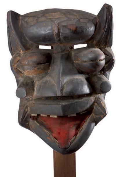 WE. (Ivory Coast) Mighty Mask classical form. In a prominent forehead, and framed by multiple projections are clearly indicated large bulging eyes, a strong nose, and open mouth revealing a huge metal teeth, and a large tongue covered with red cloth. Patina. Wood. h.: 29 cm