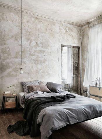 モノトーンのクッション、枕、ベッドリネンが秋らしいインテリア。壁のデザイン、飾り気のないペンダントライトも素敵ですね。