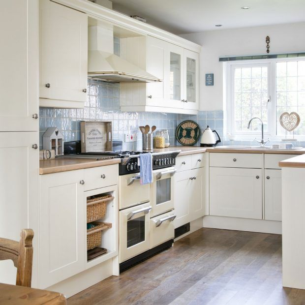 In this U-shaped kitchen, a wide window is the central anchor point of the scheme, filling the space with light and showing off classic units, and blue textured tiles in their best light. The use of wood finishes on the floor and worktops brings a warmth and cosiness to an otherwise pale decorating scheme and adds a rustic edge. 'The kitchen has plenty of cupboards and worktops, but I'd like to give it a more modern look when we come to updating it.'