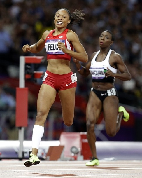 United States' Allyson Felix crosses the finish line to win the women's 200-meters final ahead of Ivory Coast's Murielle Ahoure during the athletics in the Olympic Stadium at the 2012 Summer Olympics, London, Wednesday, Aug. 8, 2012.