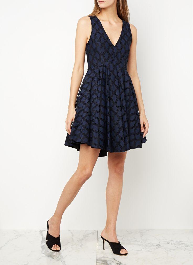 Regina A-lijn jurk van Sandro. Dit stijlvolle exemplaar is vervaardigd uit een verfijnde kwaliteit voorzien van een ruitpatroon en verrijkt met kant. Het donkerblauwe ontwerp is mouwloos uitgevoerd, heeft een V-hals en is aan de achterzijde afgewerkt met een blinde ritssluiting.