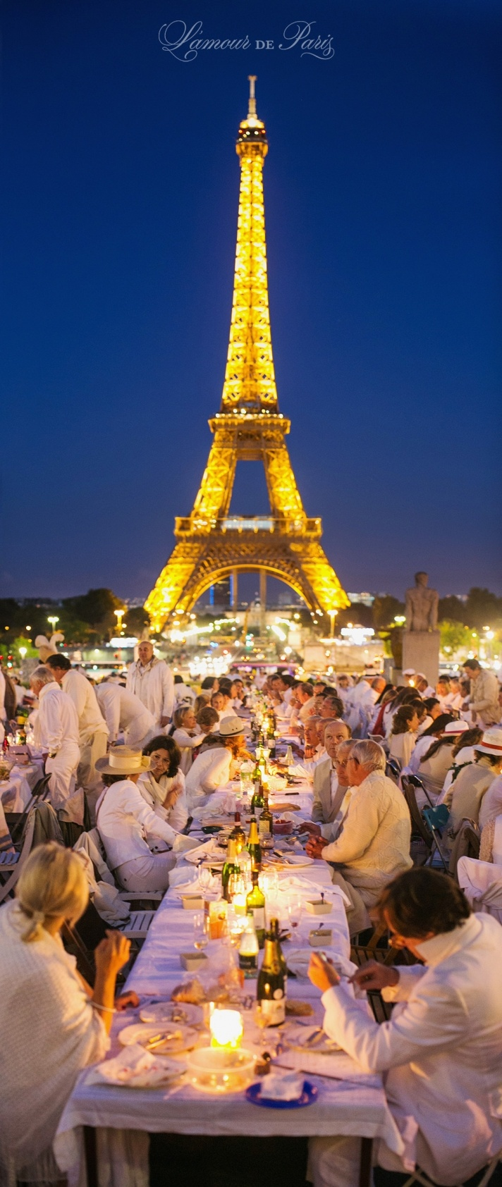 Diner en Blanc, a top secret invitiation-only flash mob in Paris, France where 11,000 people dressed entirely in white clothes spontaneously set up tables and chairs in front of historic landmarks one night a year. Photographed by Paris wedding and portrait photographer Stacy Reeves