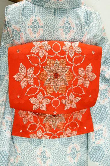 ほのかに朱色をおびた鮮やかな綺麗な赤に、ヨーロッパのビンテージレースのような装飾模様が織り出された開き名古屋帯です。