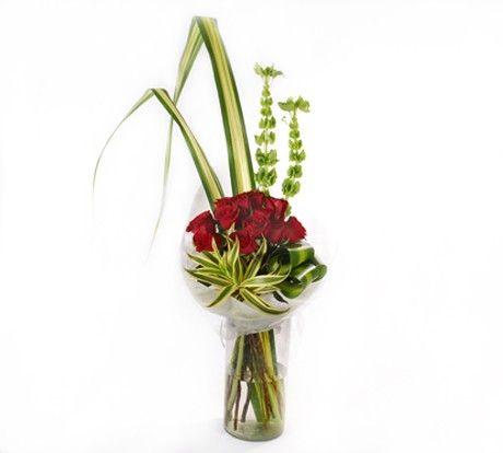 doce rosas rojas decoradas con follaje en un florero de vidrio o en papel decorativo