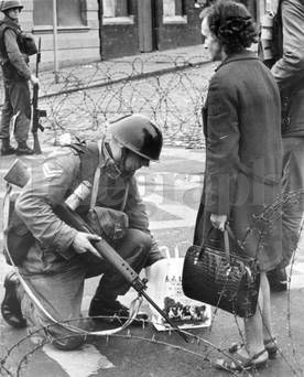 Belfast. August 1969.  A woman has her message bag searched before being allowed to re-enter the sealed off area after doing her shopping.  (16/8/69)