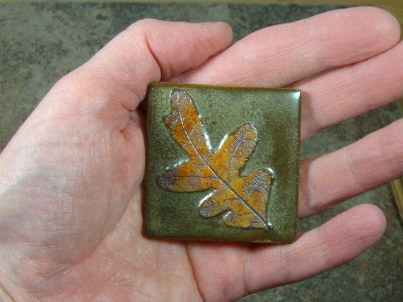 This little Oak Leaf tile is 2 x 2 and is about 3/8 thick. It is midrange stoneware, fired in an electric kiln. The back is textured, making it easily suitable for a permanent tile installation. It is glazed in olive, with underglazes and iron oxide on the leaf print. I use real leaves for the prints, so no two are ever quite the same. The tiny leaf on this tile is from a huge Oak tree we pass on our walks.  The last photo is not the tile that is for sale . . . I included it just to help...
