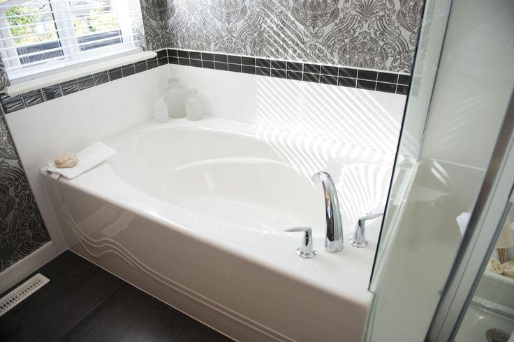 White Soaking Tub With White And Black Tile Splash Guard
