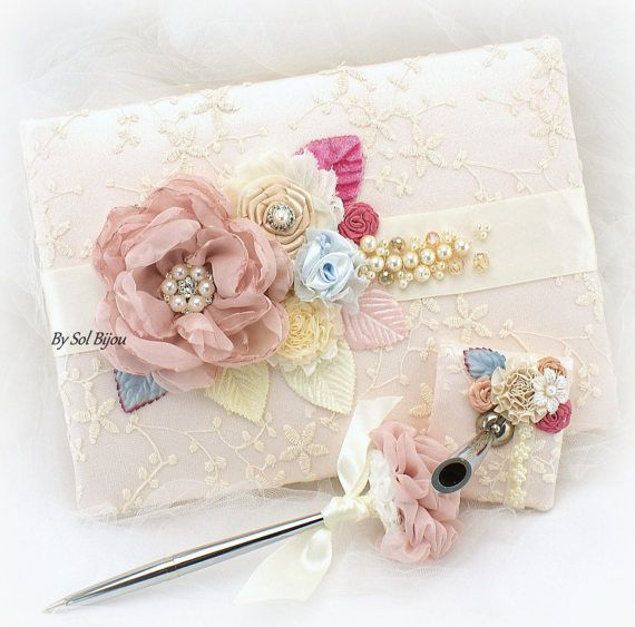 ***Made Upon Request- This listing is for the guestbook, pen base and pen. The set can be made in ANY color scheme  This is an incredibly beautiful combination of vintage tones and textures: blush, champagne, blue, pink and ivory. Made only utilizing the finest of materials. This set, like the rest of my creations, has been crafted with extreme attention to detail.  The book and pen base have been covered with a stunning ivory embroidered lace over blush fabric. The set has been decorated…