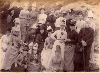 A photograph of a group of women and two men on an excursion of some kind. Granite rocks lie behind them in an unknown location. - Collections - Penlee House Gallery and Museum Penzance Cornwall UK