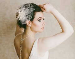 A head turning statement headpiece, handmade in our studio using the finest french net veiling along with hand-curled and tactile goose biot feathers shaped into a floral style arrangement.