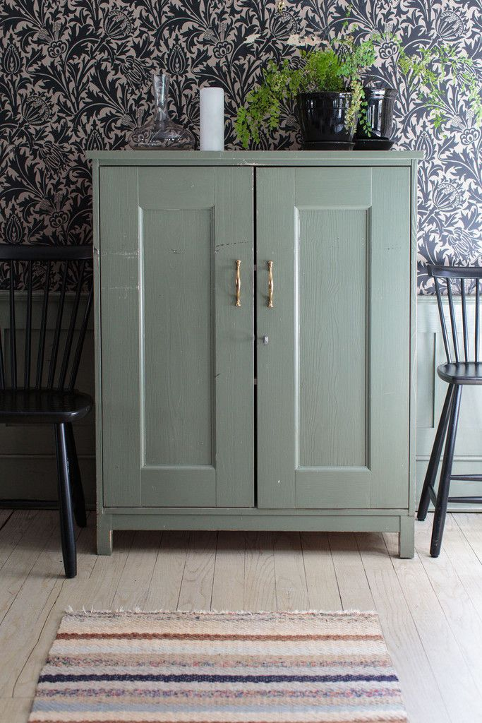 The celadon finish on an antique server coordinates with the restaurant's window trim and chair railing.