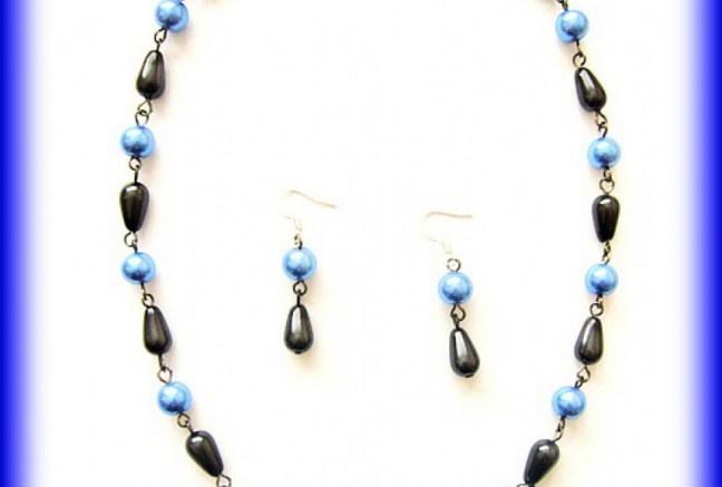 Vysoko elegantný náhrdelník. Stred tvorí tmavo modrá vinutka(stred tvorí strieborná fólia), voskové modré perličky a čierne kvapky z tlačeného skla. Hematitový pokov komponentov.  Sadu dotvárajú jemné náušnice z rovnakého materiálu ako náhrdelník.