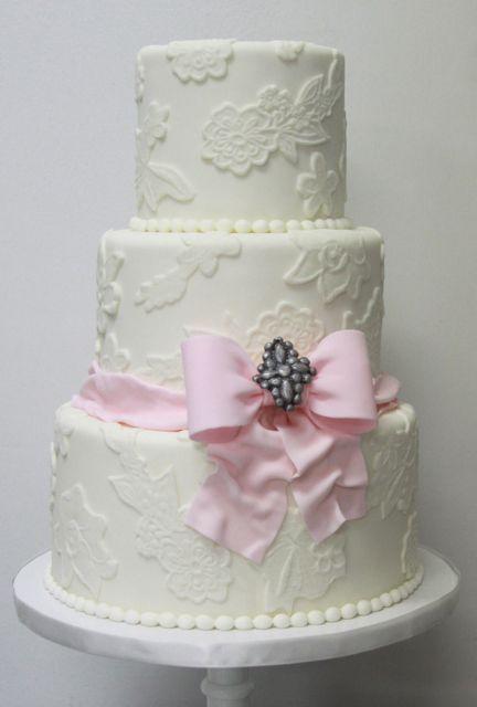 Pretty pink bow on white wedding cake