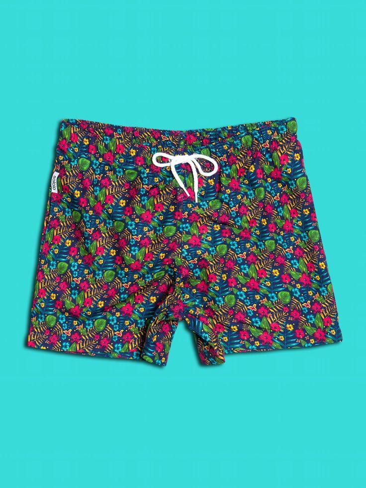 Bañador estampado con diseño de flores tropicales en color verde, rosa y turquesa, con fondo azul marino. Dos bolsillos laterales y cinturilla elástica.  www.soloio.com  #shoponline #beachwear #beachtowel #towel #print #blue #summercollection #summer #print #green #kiwi #camo