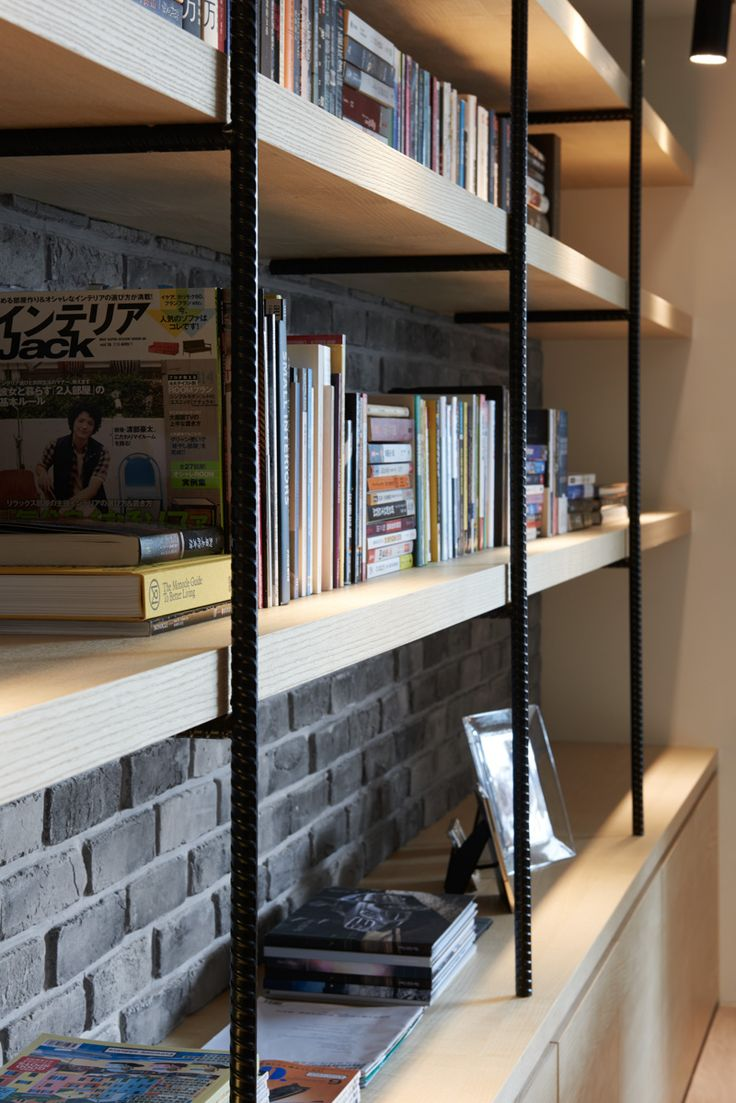 Rebar and wood bookshelves over an exposed brick accent wall enhance the industrial accents present throughout the home.