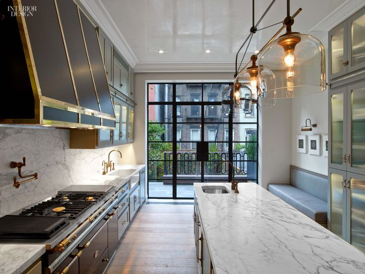 A black and gold kitchen hood stands over a black and gold French stove and a gold pot filler next to a farmhouse sink and deck mount gooseneck faucet.