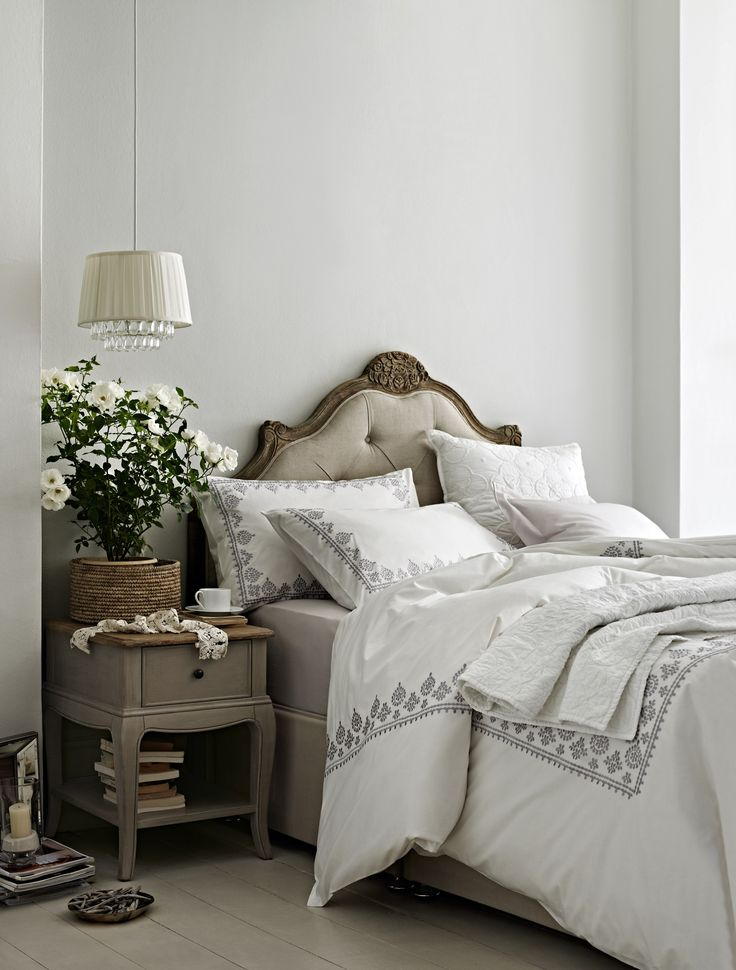 Classic white bedding edged with embroidery with a traditional head board and neutral bedroom furniture.