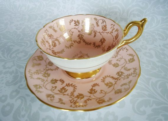 An antique (vintage) pink and gold chintz teacup and saucer set made of bone china in England. This tea cup and saucer set has a pale pink