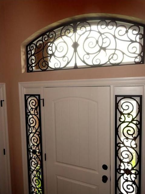 Beautiful use of faux iron for side lights and arched transom window in this entry.