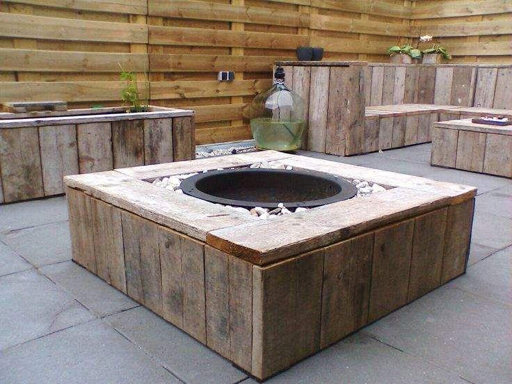 Vuurschaal in een grindbed met omtimmering van steigerhout.