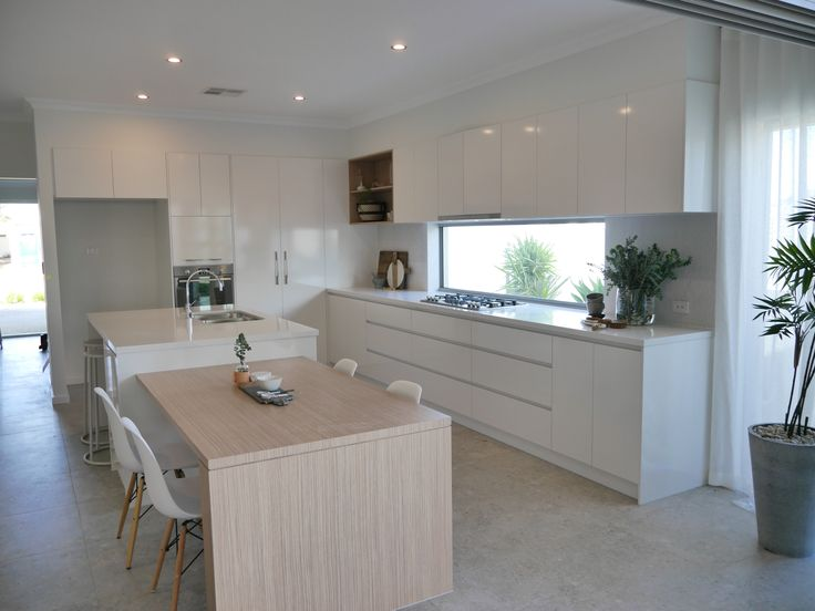 Contemporary coastal kitchen, essastone benchtops, Polar white Silk finish cabinetry and Polytec natural oak custom designed built in dining table. make a wish charity home, mandurah WA. Interiors by Colour Cube Interiors, Perth, WA.