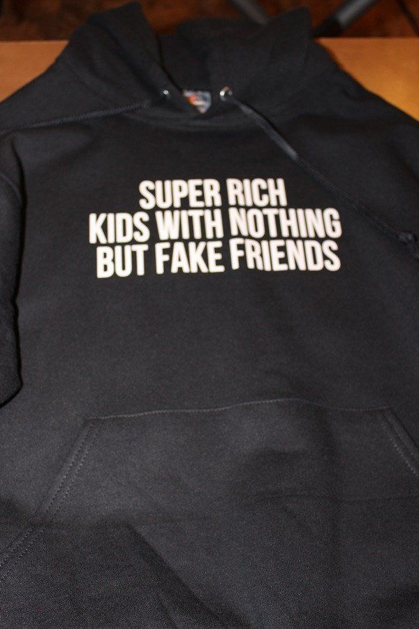 "Soft, durable and comfortable; This cotton blend black hoodie features lyrics from Frank Ocean's Super Rich Kids ""SUPER RICH WITH NOTHING BUT FAKE FRIENDS"" in white lettering on a black hoodie. Cotton"