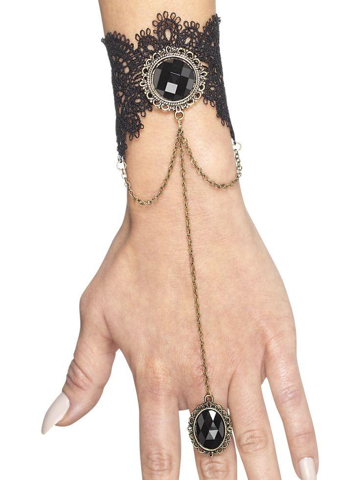 Käsikoru sromuksella. Rannekorua somistaa suuri musta korukivi ja hienona yksityiskohtana rannekorussa on ketjulla kiinni oleva sormus.