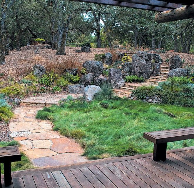 This California garden blends Japanese and Western design. The author graded the site, built the path, and created the stone group using principles of Japanese gardening learned in Kyoto. The client, an artist and painter, has used the slopes and the boulders as a foil, creating a planting layout which turns to Western horticultural ideas for inspiration.