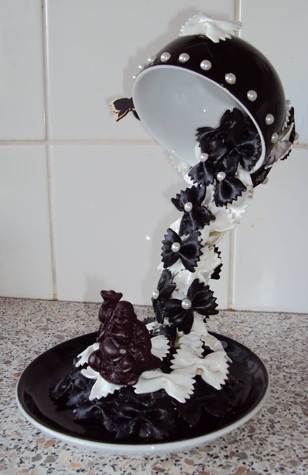 DIY Black and white pasta bowtie waterfall falls from a floating black bowl trimmed with pearls. Stunning piece of art.   I would get rid of the figurine and use it for a black and white Christmas party buffet centerpiece. Zwevend kopje