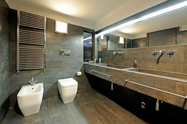 Интерьер в стиле лофт напоминает заводские помещения и склады. Поэтому, оформляя ванную комнату в этом стиле, прятать трубы и другие коммуникации нет необходимости. Окрашенные в яркий цвет, они смогут стать акцентным элементом в помещении. В отделке характерны кирпич, плитка под бетон, под дерево и с имитацией металла. Для таких ванных комнат идеально подойдут душевые кабины из стекла. Хромированные элементы декора, постеры, светильники в виде лампочек - все это будет прекрасным дополнением…