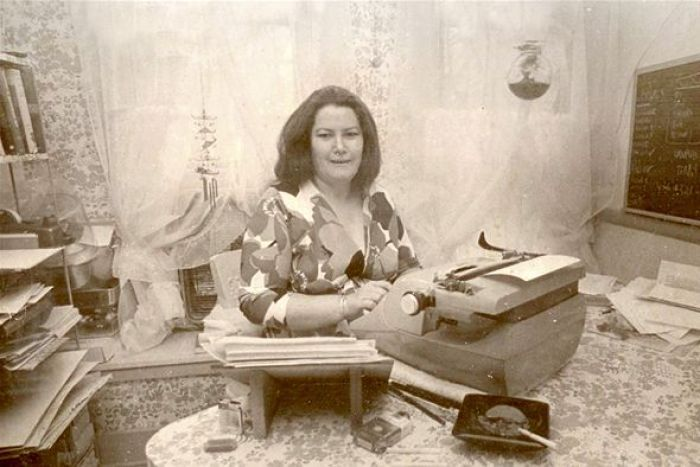 Colleen McCullough sitting at a typewriter