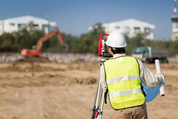 land survey and asian civil engineer working with his equipment