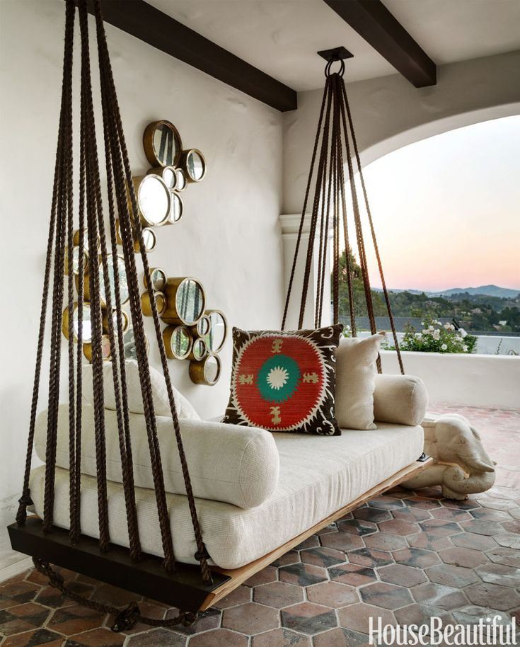 Responding to her clients' request for a swing where they could enjoy the view of Mount Tamalpais and the hills of San Francisco in this Spanish Colonial home, designer Erin Martin used rope, metal rings, and wood to improvise this hammock/divan on the loggia.