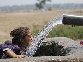 Menina se refresca na água, neste sábado (21), em Jammu, na Índia (Foto: AP Photo/ Channi Anand)