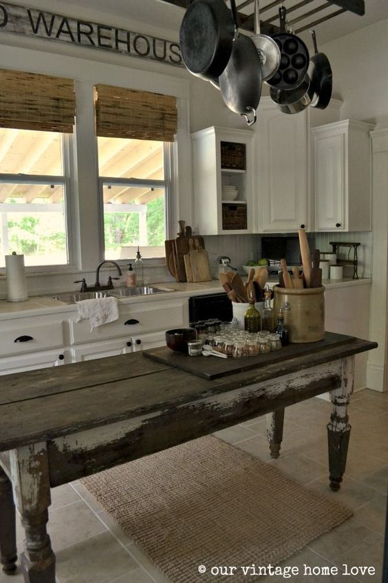 Old Farm Kitchen With A Weathered, Narrow Harvest Table For An Island.