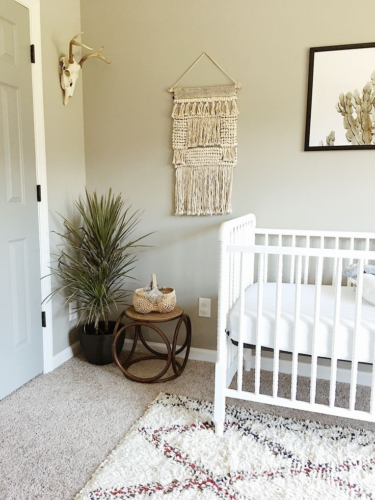Boho neutral cactus desert theme nursery decor. Real deer head. Jenny Lind crib. Woven wall hanging. Dragon tree. Bentwood stool.