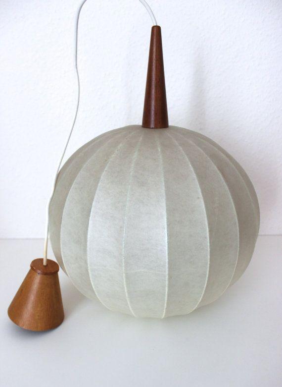Wunderschöne Cocoon-Lampe aus den 50er/60er Jahren. Der Schirm besteht aus einem Metall-Gerüst, auf welches das Cocoon Gewebe gespannt ist. Oberhalb des Lampenschirm ist ein Teakholzkegel, durch welchen das Stromkabel führt.  Cocoon besticht durch seine spezielle Materialeigenschaft Die Oberfläche weist eine besondere Beschaffenheit auf und erhält durch die faserartige Struktur einen besonderen Look. Darüber hinaus besticht Cocoon durch seine Transparenzeigenschaften: als Diffusor-Material…