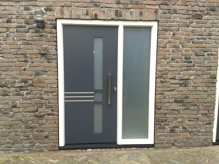 Moderne vleugeloverdekkende kunststof voordeur met zijlicht. Afgewerkt in antraciet met aluminium details deurgreep.