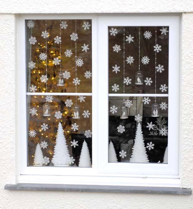 Décorer la fenêtre avec des guirlandes de découpe de flocons et coton, et village en bas.