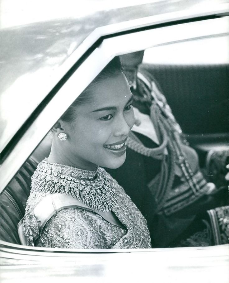 Her  Majesty Queen Sirikit of Thailand sitting in a car with His Majesty Bhumibol Adulyadej .