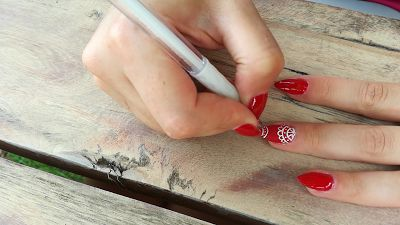 Blondynka online: Czerwony, wyrazisty lakier hybrydowy i białe ręcznie wykonane zdobienia.