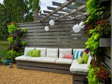 With a living wall draped with plants and all-weather materials, the backyard pergola provides a shaded spot to relax and gather.