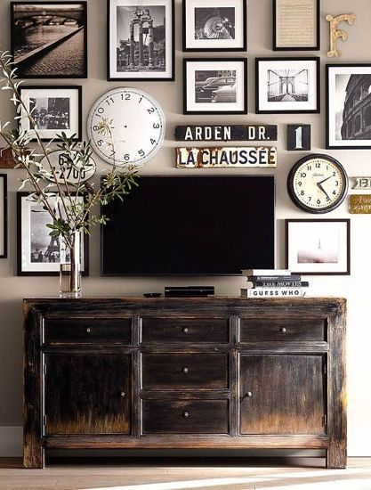 Disguise a flat screen, wall-mounted TV in a fab gallery wall of black & white. Ground it with a sturdy buffet in a soft, distressed wood. So smart.