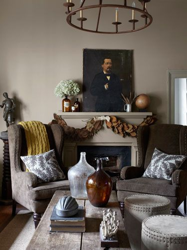 Corduroy-upholstered wing chairs, fern-print pillows, and antique demijohns lend a cozy feel to this subtly dark living room.